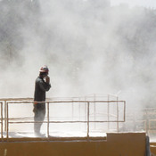 A worker stands on top of a storage bin on July 27, 2011, at a drilling operation in Claysville, Pa. The dust is from powder mixed with water for hydraulic fracturing. Researchers studying workers' exposure to chemicals at drilling sites found very high levels of silica in the air at some locations.