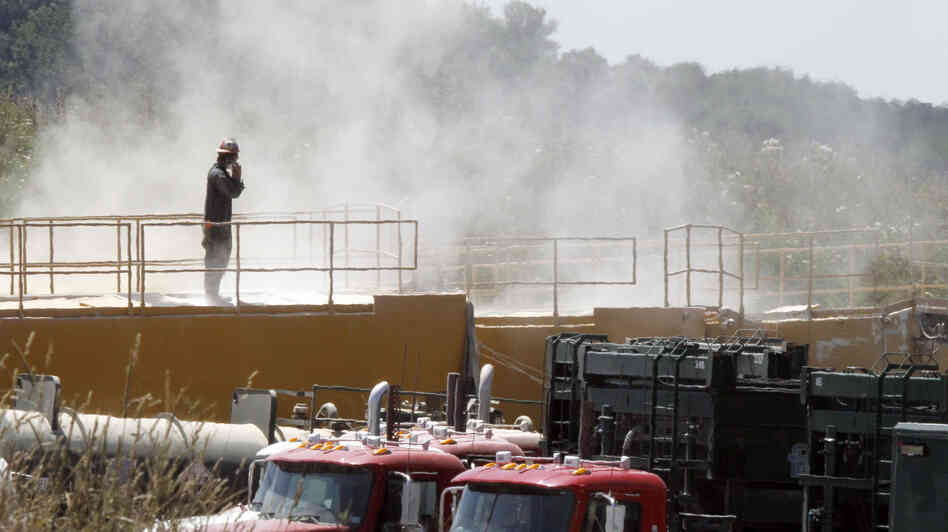 A worker stands on top of a storage bin on July 27, 2011, at a drilling operation in Claysville, Pa. The dust is from powder mixed with water for hydraulic fracturing.