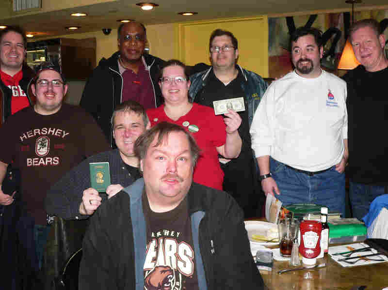 Avid users of wheresgeorge.com gather at Kabooz's Bar and Grill at New York's Penn Station to trade dollar bills and send off a group that's going on a cross-country train trip to Los Angeles.