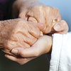 Elderly and young person holding hands