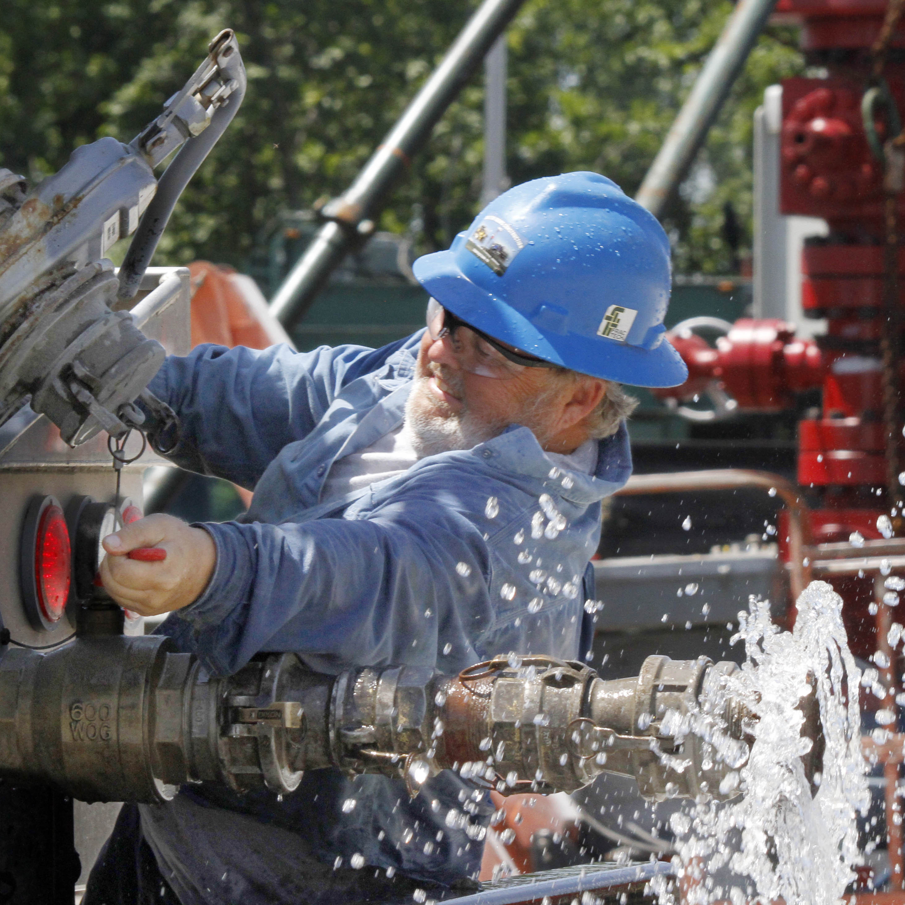 A local contractor closes the valve on his tanker truck on July 27, 2011, after watering the roads to help keep down dust at a hydraulic fracturing operation in Claysville, Pa.