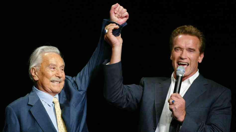 Arnold Schwarzenegger raises the arm of Joe Weider, the creator of the Mr. Olympia