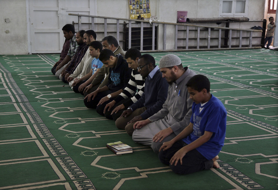 Egyptian men and boys pray at a mosque in Assiut, southern Egypt, that serves as the headquarters for Gamaa al-Islamiya, a group that once waged a bloody insurgency, attacking police and Christians in a campaign to create an Islamic state. Now the Islamist group says it's determined to ensure law and order in the area.