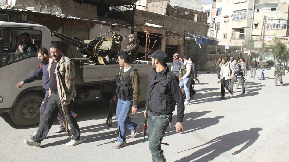 Rebels from the Free Syrian Army walk on a street in Damascus in this picture provided by Shaam News Network and taken March 23. The Syrian capital came under mortar fire on Sunday and Monday. (Reuters /Landov)