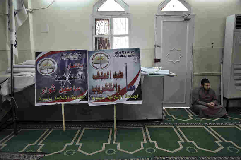 "An Egyptian man waits to join afternoon prayers at the mosque used as Gamaa al-Islamiya's headquarters in Assiut, southern Egypt. The banners feature slogans such as ""we are against violence and destruction"" and ""shame to thugs."""