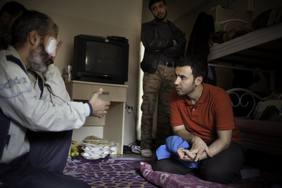 Mulham al-Jundi (right), who works for the nongovernmental organization Watan, visits an injured fighter at a recovery home for Free Syrian Army veterans. Jundi is one of the young Syrian humanitarian workers based in Reyhanli, Turkey, near the Syrian border. (Jodi Hilton for NPR)