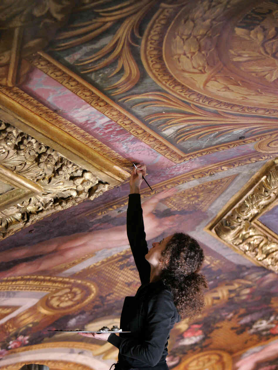 Restorer Nicoletta Rinaldi works on the ceiling of the Hall of Mirrors at the Versail