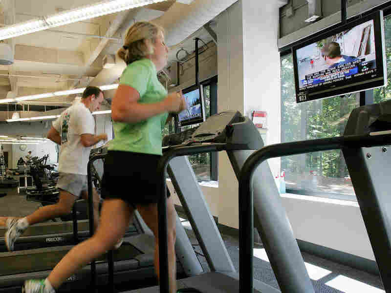 Chick-Fil-A employees Jennifer Cummins, right, and Joshua Figaretti work out in the gym during lunch at the company's corporate headquarters office in Hapeville, Ga. Increasingly employers are offering health plan incentives to encourage healthy behaviors from workers.