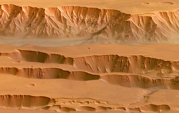 Coprates Chasma in the Valles Marineris on Mars, photographed by the Mars Express spacecraft. Appearing in the top half of this image, it ranges from 60-100 km wide and drops 8-9 km below the surrounding plains.