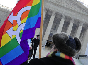 A pro-gay-marriage protester stands in front of the Supreme Court on Tuesday, the first of two days of oral arguments on chal