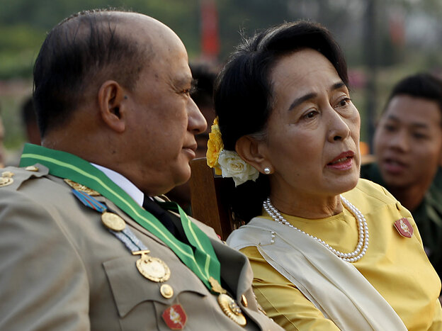 Opposition leader Aung San Suu Kyi (right) speaks with Maj. Gen. Zaw Win, deputy minister for border affairs, during a ceremony Wednesday marki