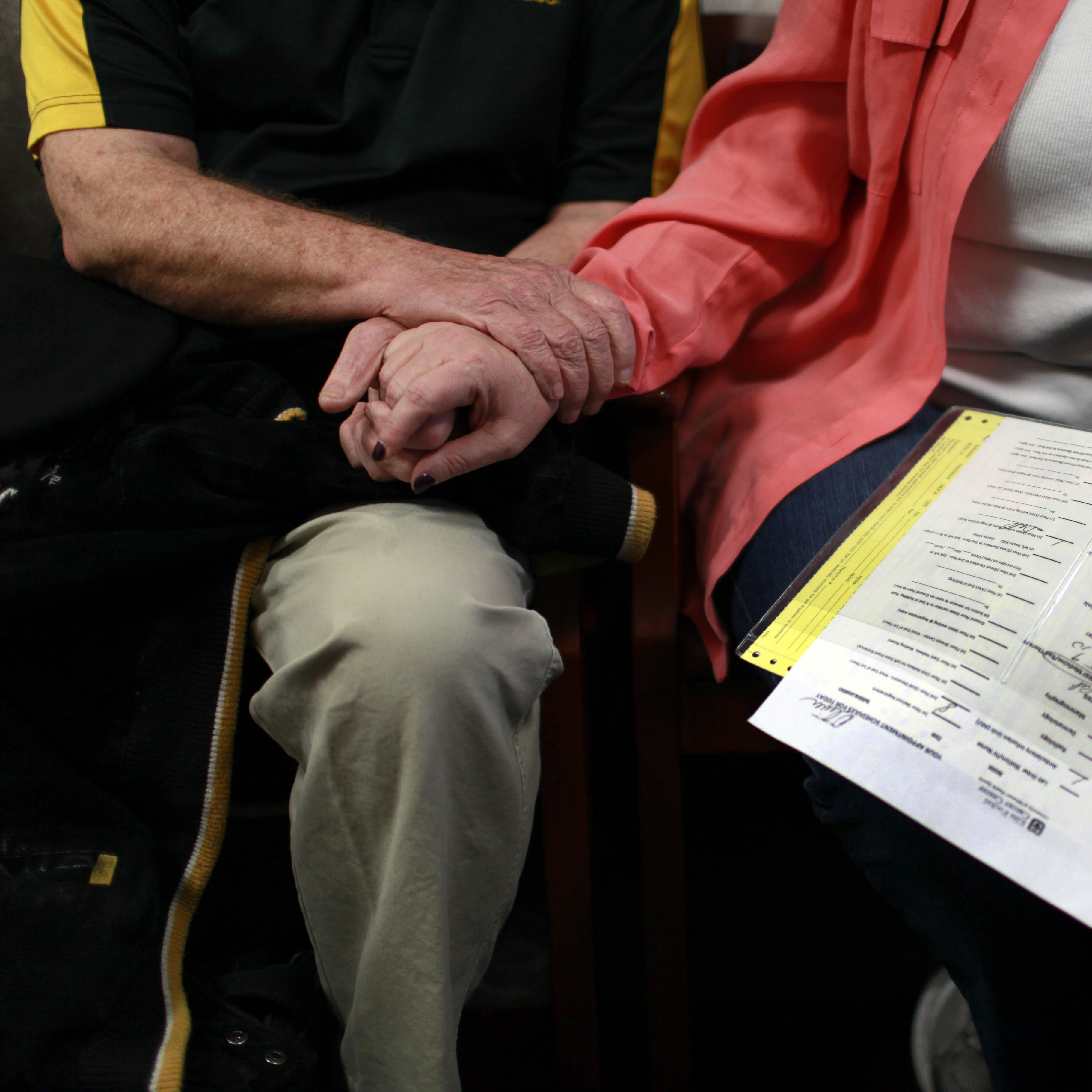In a Tuesday, Jan. 17, 2012 photo, David Oliver, left, holds his wife's hand as Debra Parker Oliver clutches her husband's medical records while they wait for David to undergo medical tests at Ellis Fischel Cancer Center in Columbia, Mo.