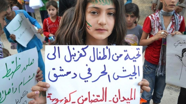 "In this image taken July 16, 2012, and provided by Edlib News Network, a Syrian girl holds a poster that reads, ""Greetings from Kfarnebel's children to the Free Syrian Army soldiers in Damascus,"" during a demonstration in Kfarnebel, Syria. The image was part of an ""inside rebel-held Syria"" series of stories by NPR's Kelly McEvers. (AP)"