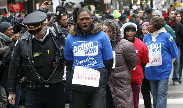 A Chicago police officer takes several protesters into custody on Wednesday, during an act of civil disobedience during a march and demonstration of opponents to a plan to close 54 Chicago Public Schools.