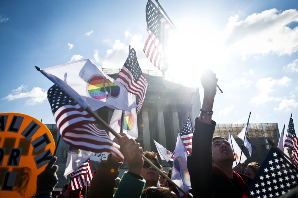 Supporters wave American and gay rights flags outside the Supreme Court during the Defense of Marriage Act case hearings on Wednesday in Washington, D.C.