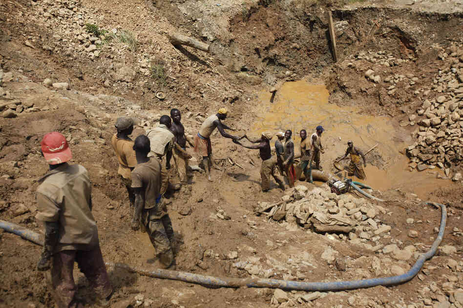 Gold miners pass up pans of sediment from an open-cast mine near the town of Mongbwalu, in the eastern Democratic Republic of Congo, last April.