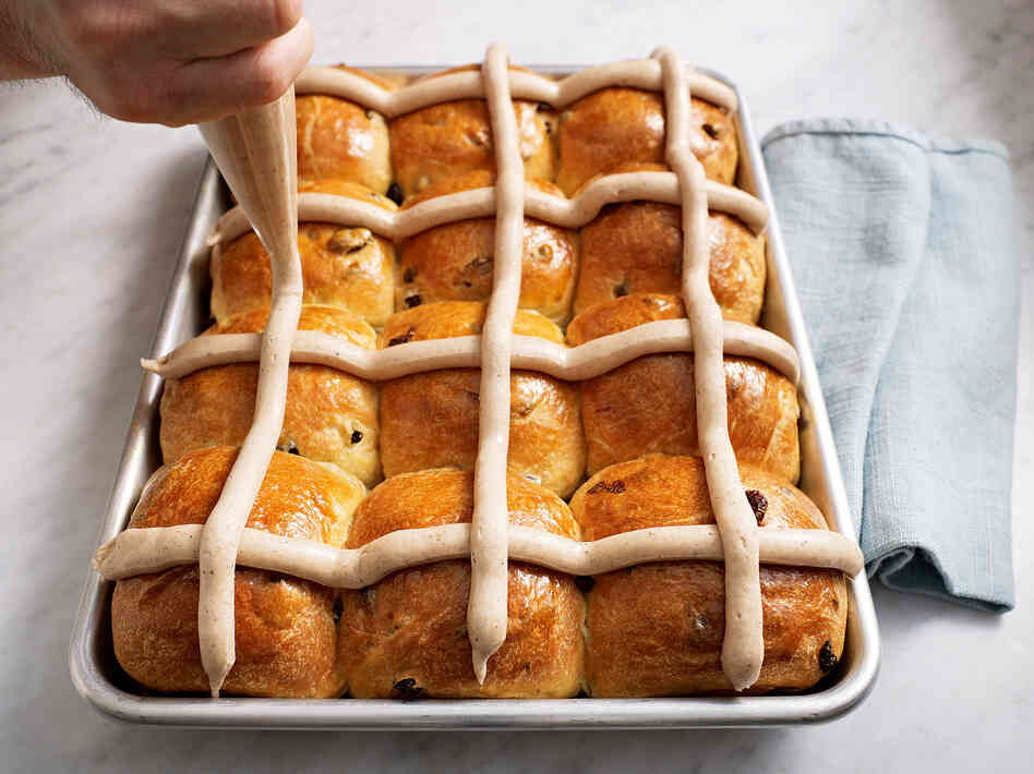 "The Bouchon Bakery cookbook demonstrates how to apply the frosting ""cross"" on a pan of hot cross buns."