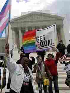 In this photo taken Wednesday, March 27, 2013, demonstrators holding flags chant in front of the Supreme Court in Washington.  (AP Photo/. (AP Photo/Jose Luis Magana)