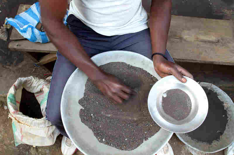 A Congolese miner sifts through ground rocks to separate out the cassiterite.