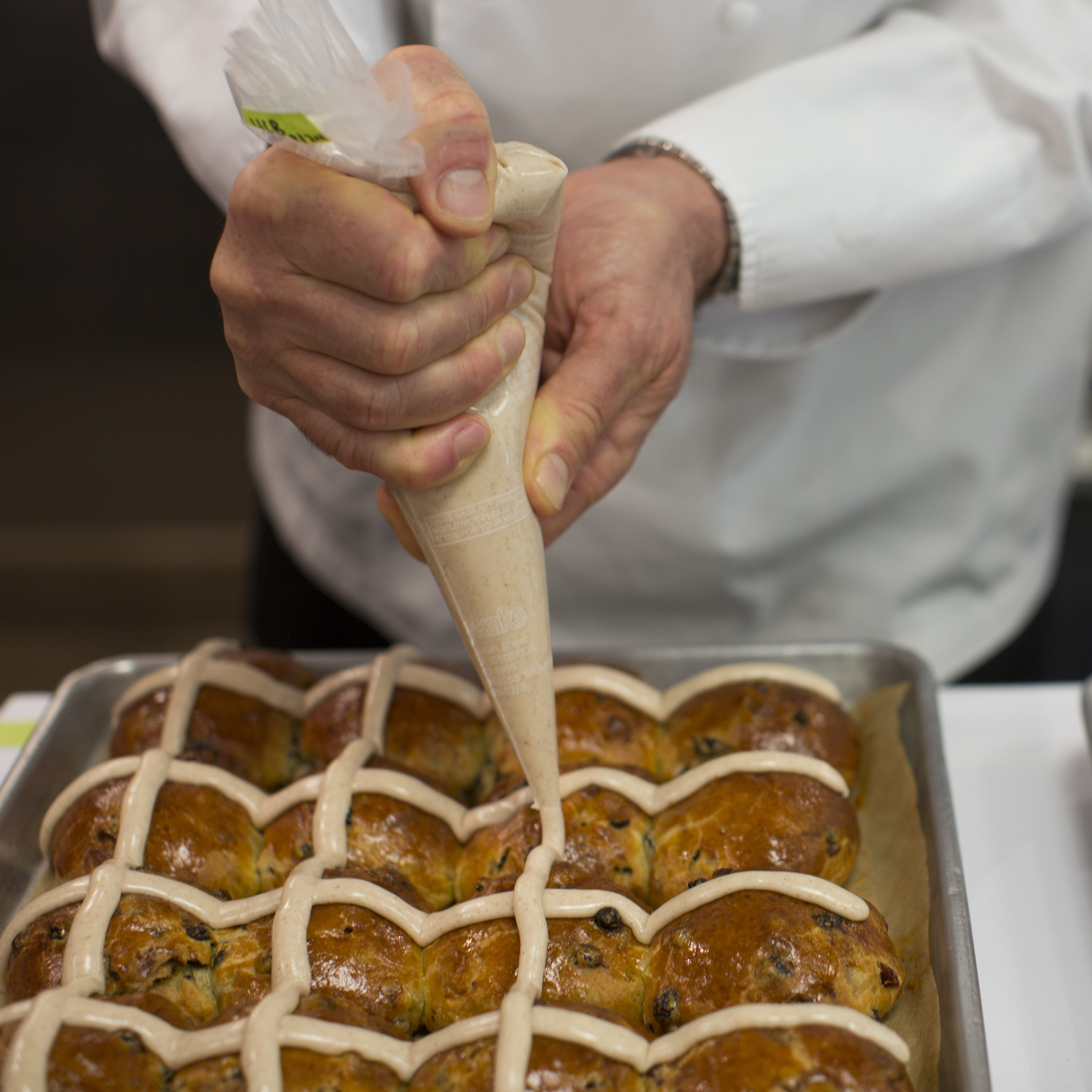 Chef Thomas Keller demonstrates how to apply homemade icing to his hot cross buns.