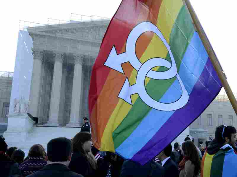A supporter of same-sex marriage holds a rainbow flag outside of the Supreme Court on the day the high court hears the case challenging the Defense of Marriage Act.