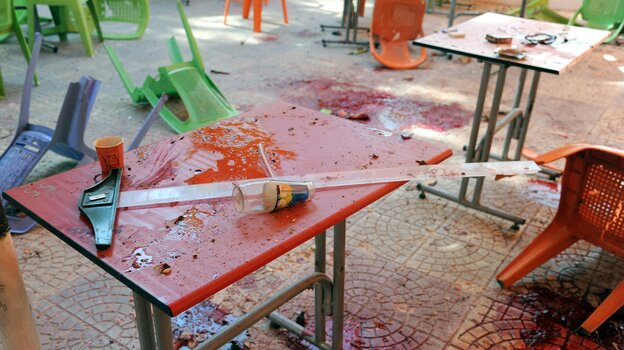 A photo released by the official Syrian Arab News Agency shows bloody tables and chairs in a Damascus University cafeteria that was struck by a m