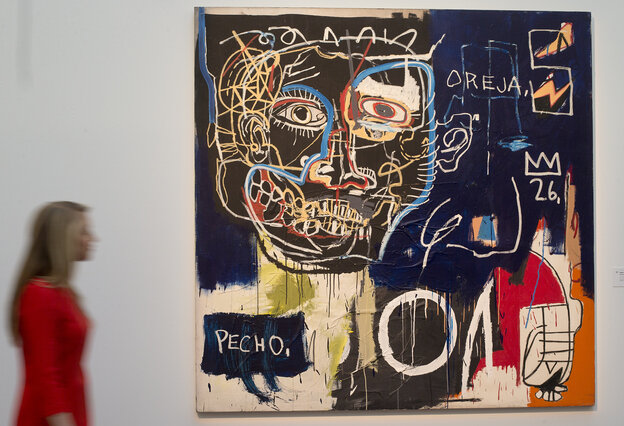 """A Sotheby's employee walks past a work by Jean-Michel Basquiat titled """"Untitled (Pecho/Oreja)"""" at the auction house."""