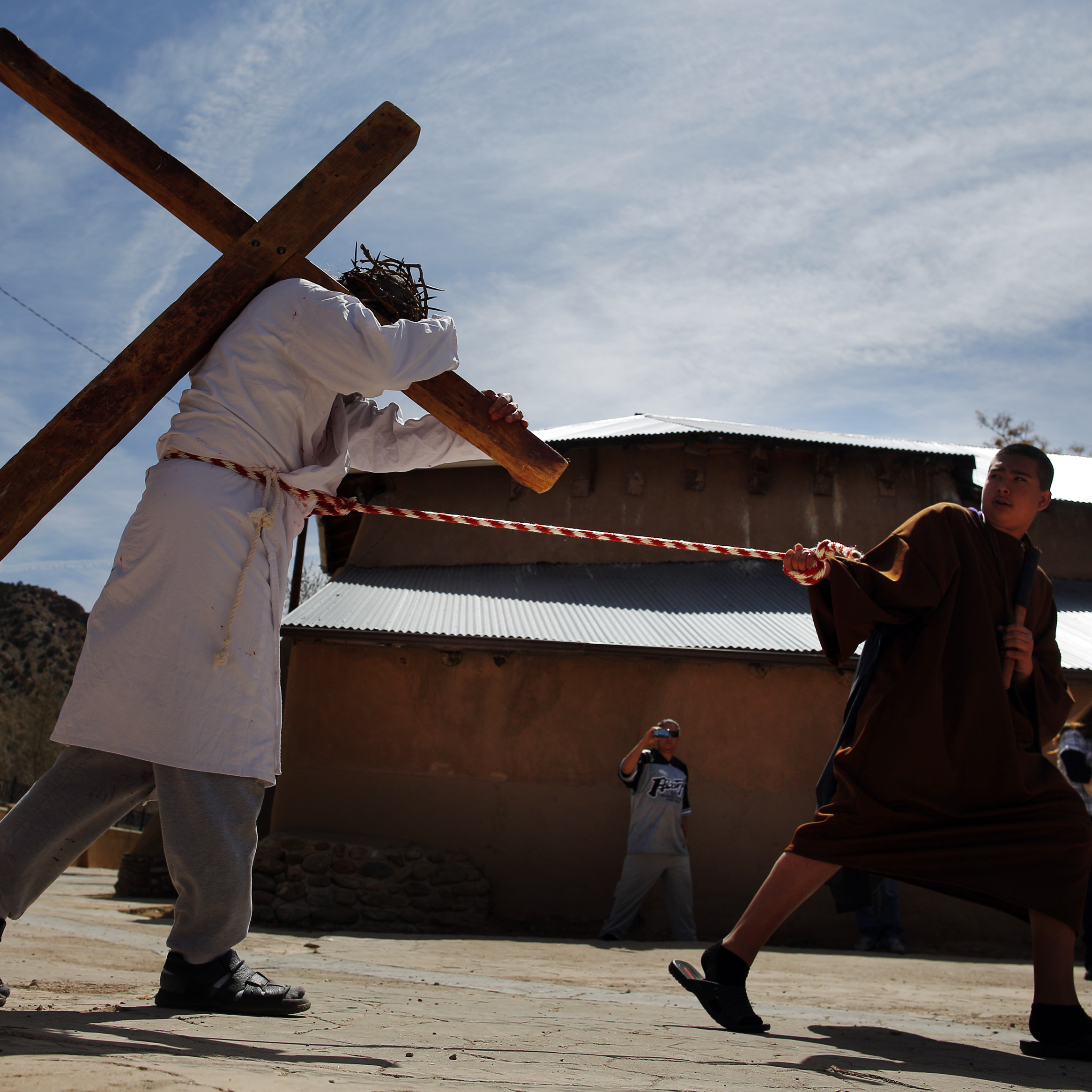 Students playing the roles of Roman soldiers lead a man playing the role of Jesus during a re-enactment of the Stations of the Cross at the Sanctuary of Chimayo in New Mexico on Thursday.