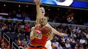 Brandon Triche (No. 20) of the Syracuse Orange goes to the hoop against Cody Zeller of the Indiana Hoosiers during their teams' game Th