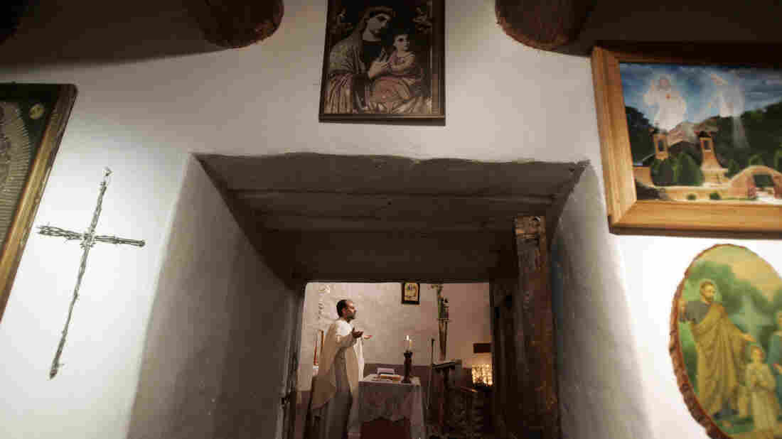 The Rev. Julio Gonzalez leads Easter Mass at El Santuario de Chimayo in 2007. Thousands of visitors make a pilgrimage to visit the small chapel annually every Easter weekend. Many people believe that the dirt inside the chapel has healing powers.