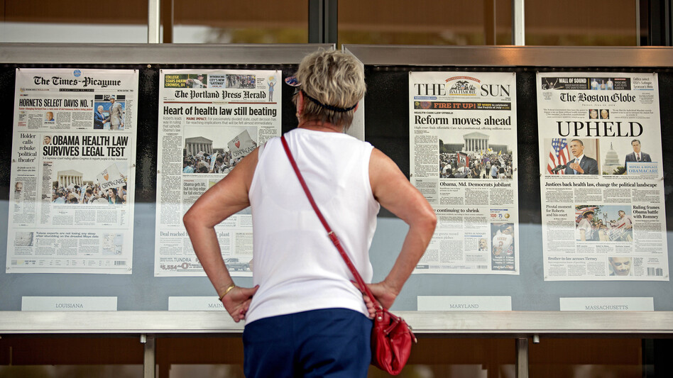 Joy Reynolds of San Diego looks at the newspapers on display at the Newseum in Washington, D.C., on June 29, 2012, following the Supreme Court ruling on President Obama's health care law. (David Goldman/AP)