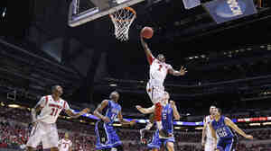 Louisville guard Russ Smith (2) goes up with a layup against Duke defenders during the first half of the Midwest Regional final in the NCAA college basketball tournament Sunday in Indianapolis.