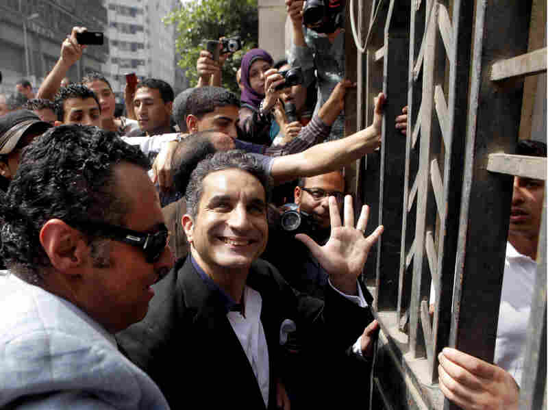 Television satirist Bassem Youssef waves to supporters as he enters Egypt's state prosecutors office to face accusations of insulting Islam and the country's Islamist leader in Cairo on Sunday.