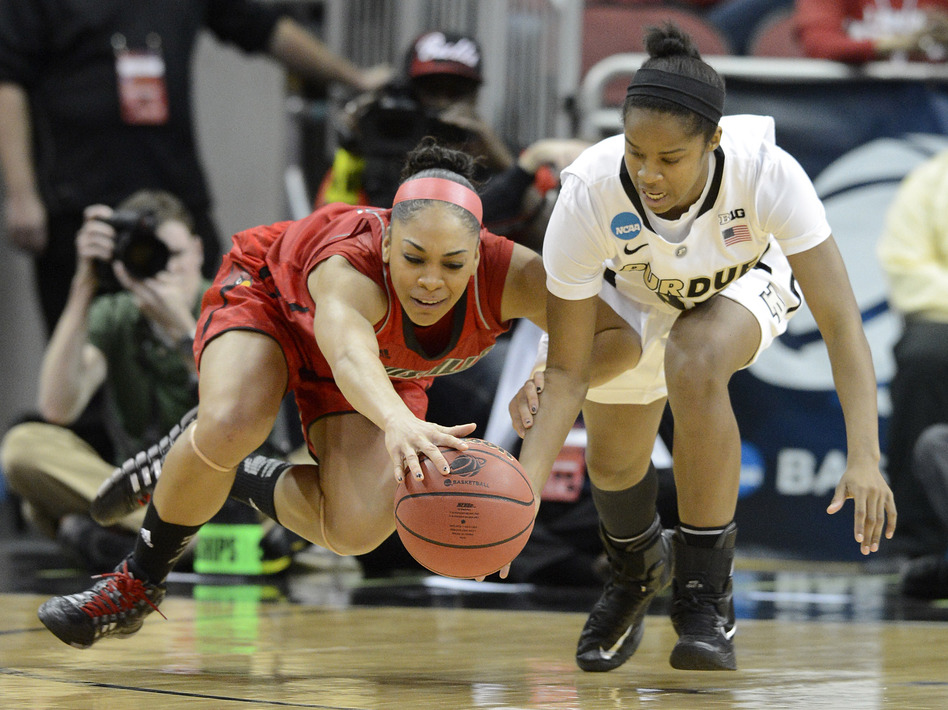 Louisville's Bria Smith, left, battles Purdue's April Wilson for a loose ball during their second-round game in Louisville, Ky., Tuesday. (AP)