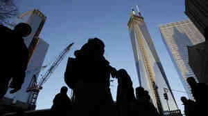 People pass the World Trade Center construction site in New York. Debris from the fallen towers will be sifted for victims' remains beginning Monday.