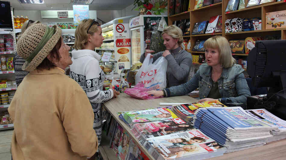 The owner of a Russian market helps customers in Limassol, Cyprus. Many middle-class Russians here say their community is being unfairly depicted as a group of money-laundering oligarchs.