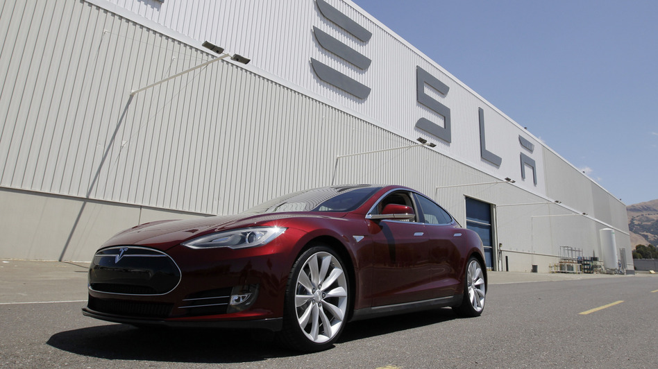 A Tesla Model S drives outside the Tesla factory in Fremont, Calif., on June 22. The electric car was named Automobile of the Year by Automobile Magazine and Car of the Year by Motor Trend. (AP)