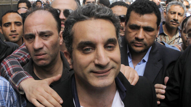 A bodyguard secures popular satirist Bassem Youssef, who has come to be known as Egypt's Jon Stewart, as he enters Egypt's state prosecutors office on Su