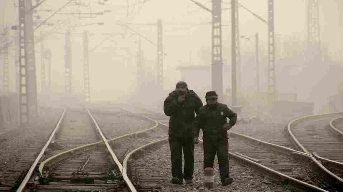 Men walk along a railway line in Beijing on Jan. 12, as air pollution reached hazardous levels.