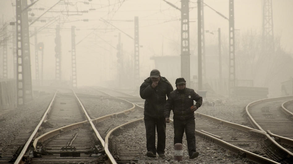 Men walk along a railway line in Beijing on Jan. 12, as air pollution reached hazardous levels. (Wang Zhao/AFP/Getty Images)