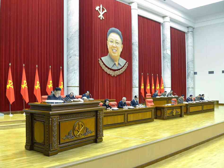 North Korea's KCNA news agency released this photo Monday, saying it shows leader Kim Jong Un (at left) speaking during a plenary meeting of the Central Committee of the DPRK in Pyongyang. Hanging above is the image of his father, former leader Kim Jong Il, who died in 2011.