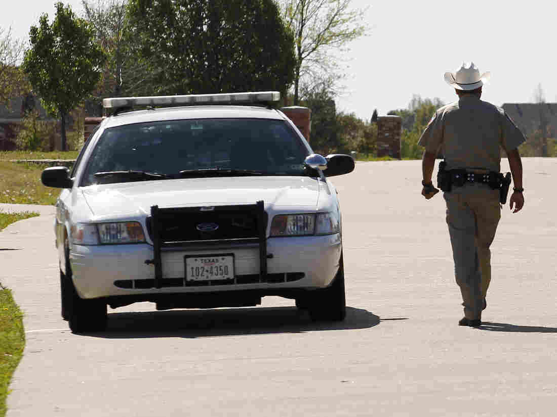 A deputy sheriff walks down the street where the home of Kaufman County District Attorney Mike McLelland is located in Forney, Texas. McLelland and his wife, Cynthia, were shot dead in their home over the weekend.