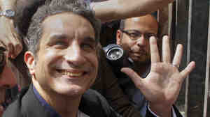 Popular satirist Bassem Youssef, who has come to be known as Egypt's Jon Stewart, waves as he enters Egypt's state prosecutors office on Sunday.
