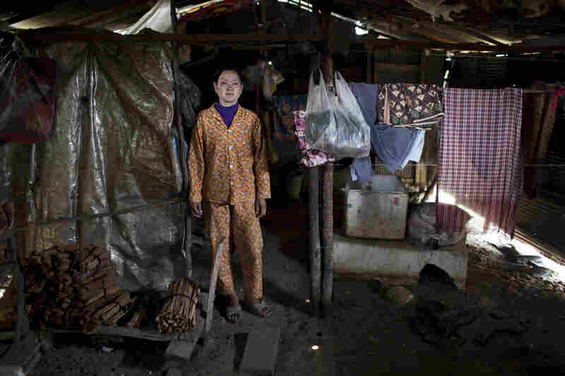 Sriv Keng, 39, stands inside her family's former home, a long garden shed with no proper water system and a floor of hard-packed dirt.
