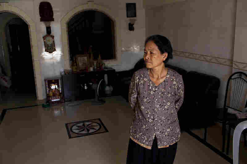 Eng Sreng stands in the family's new home with tile floors and indoor plumbing.