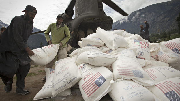 Pakistani aid workers offload USAID food supplies from an Army helicopter in Kallam Valley during catastrophic flooding in 2010. (AFP/Getty Images)