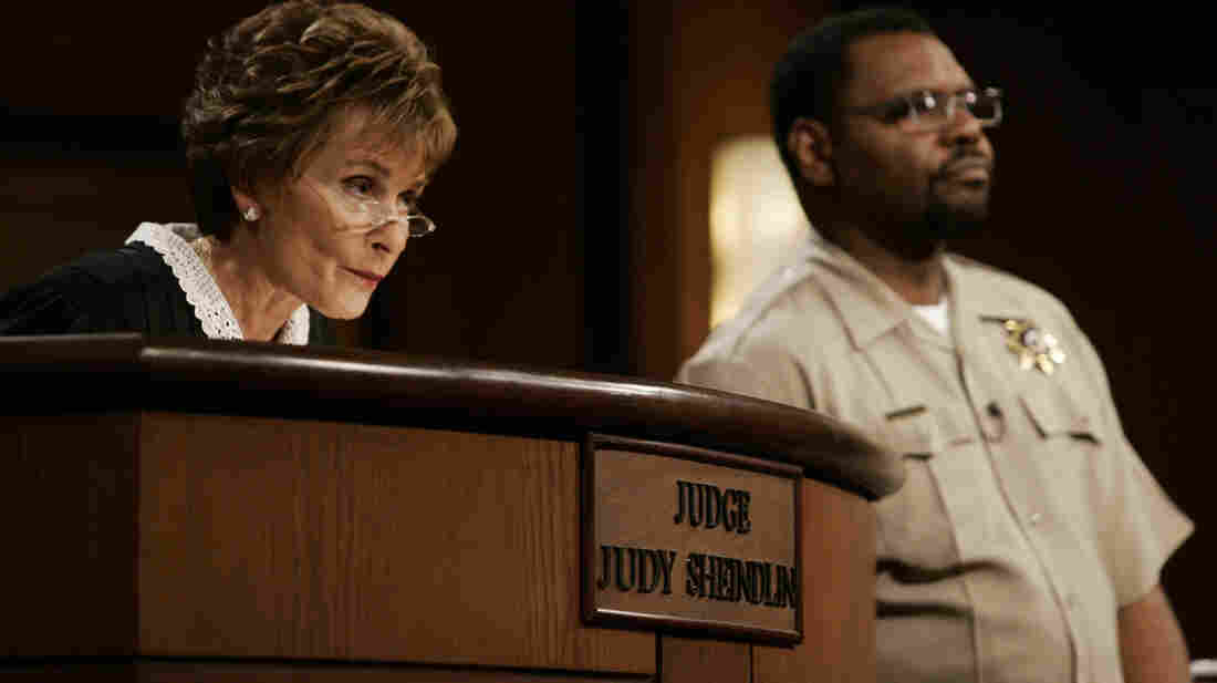 Judge Judy Sheindlin, seen here in 2006, presides over a case as bailiff Petri Hawkins Byrd listens.