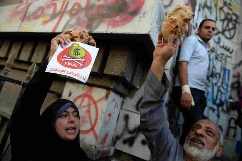 "Egyptian protesters hold bread along with fliers reading ""Danger, no to loans that lead to poverty"" during a rally Wednesday in Cairo. An International Monetary Fund delegation is in Cairo for talks on a loan needed to lift Egypt's economy out of crisis."
