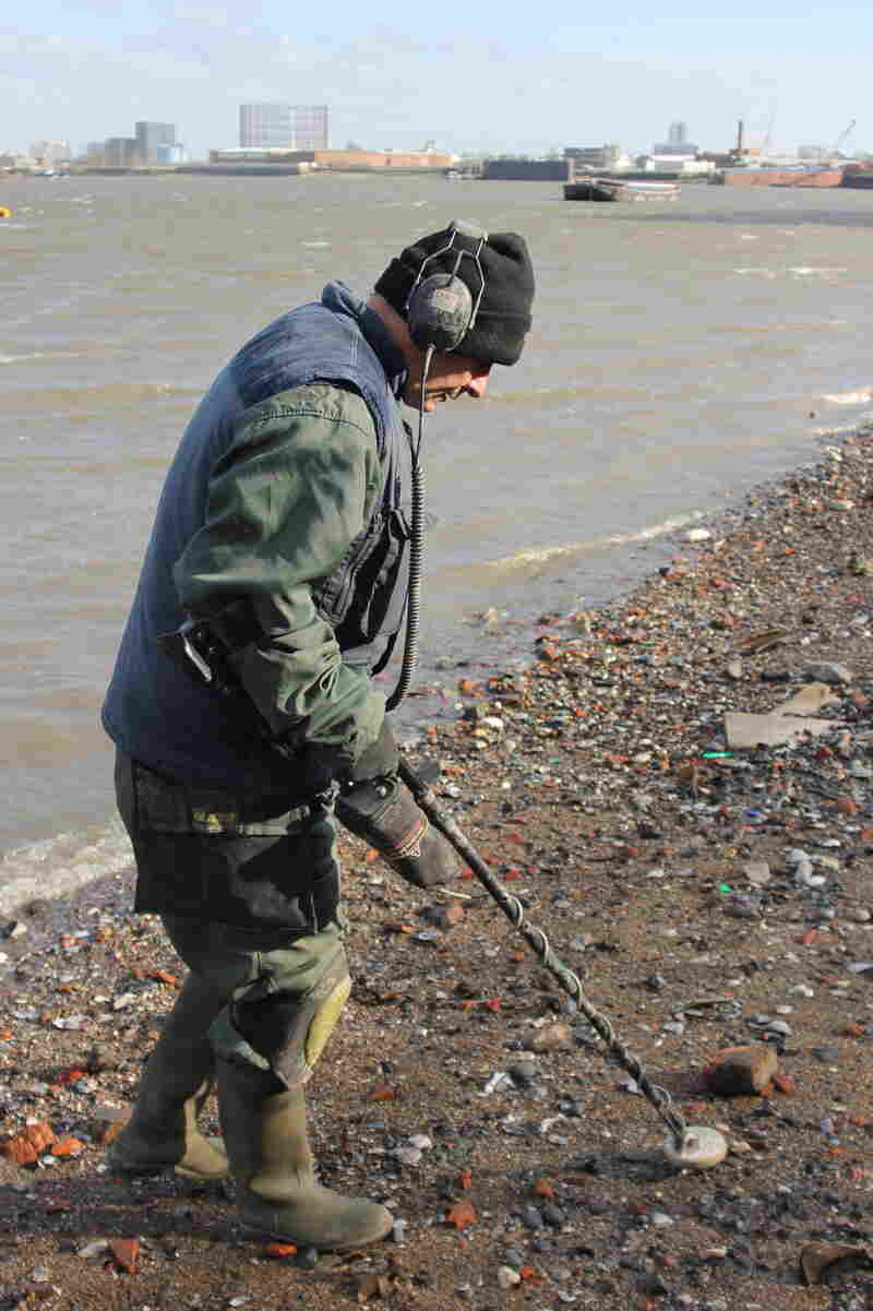 Mike Woodham uses a metal detector to search for historic artifacts on the banks of the Thames in London. Mudlarks like Woodham contribute important objects to museums, but some think their methods are too destructive.