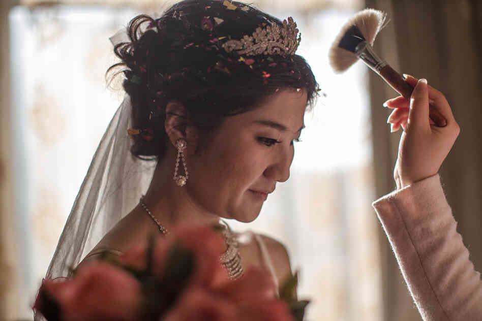 Lucy Wang gets her makeup touched up before her wedding ceremony at a Beijing restaurant. Wa
